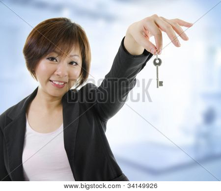 Mid adult Asian woman arms out holding a new key