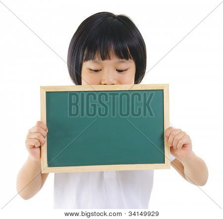 7 years old pan Asian school girl covered her mouth with blackboard on white background