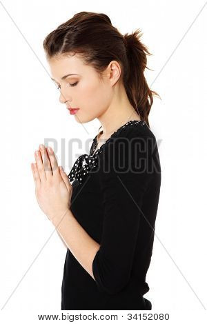 Young beautiful woman is praying. Isolated on the white background.