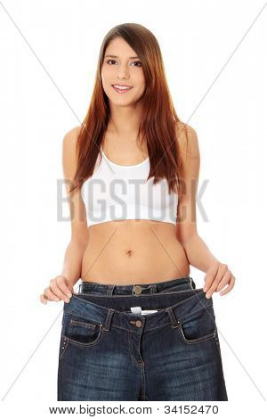 Young beautiful woman is smiling and showing too big trousers. Isolated on the white background.
