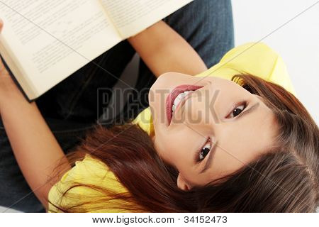 Student girl is smiling and sitting with book on her knee, looking up.