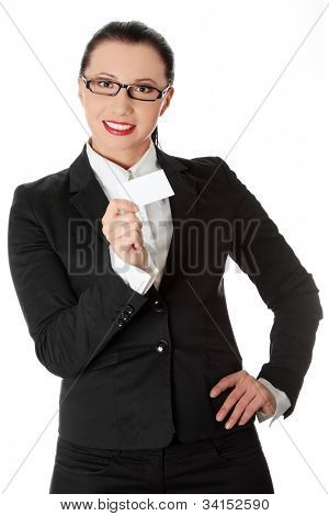 Young beautiful businesswoman is showing businesscard.  She's standing and wearing black suit and glasses. Isolated on the white background.