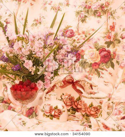 Vintage tea in elegant cups, raspberry and flowers
