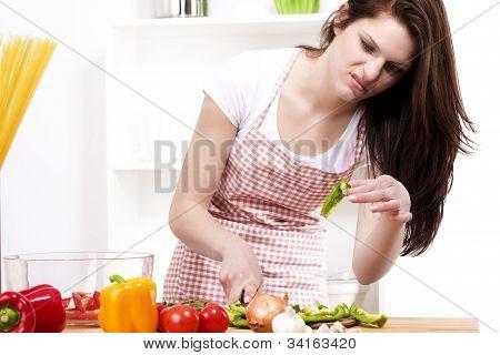 Junge Frau ist misstrauisch über den paprika