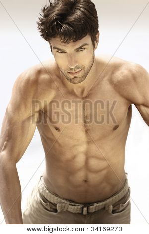 Portrait of a sexy male model without shirt revealing very muscular body