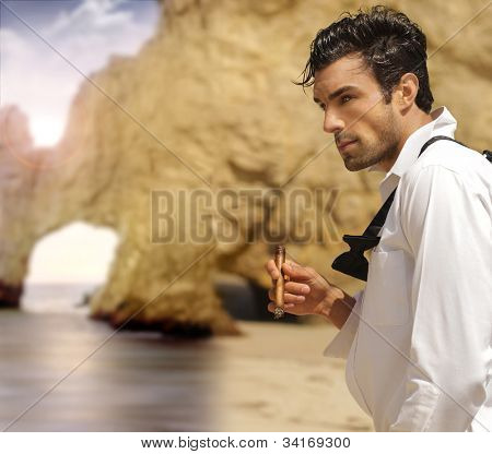 Sexy masculine man in formal clothes smoking cigar on exotic beach