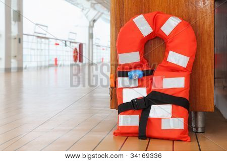 Singular orange life jacket stands on deck of cruise passenger liner; close up
