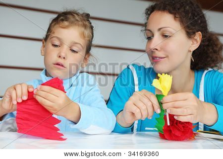 Mother and daughter sit at table and make artificial flower of tissue paper; focus on girl