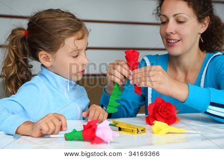 Happy mother and daughter make artificial roses of tissue paper; focus on girl