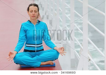 Barefoot woman wearing in blue sports suit sits on cruise liner deck and meditates