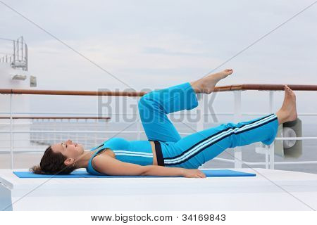Young barefoot woman wearing in sports suit lies on cruise liner deck and does exercise