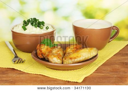 Mashed potato in the bowl and roasted chicken wings in the plate and cup with milk on colorful napkin on wooden table close-up