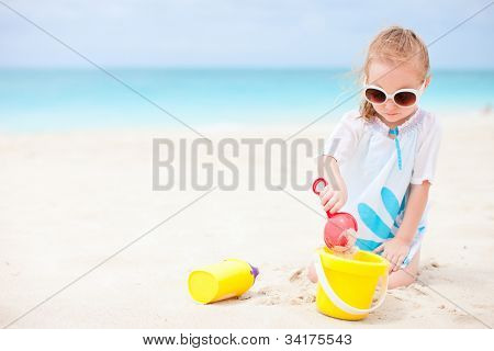 Adorable little girl with beach toys on vacation