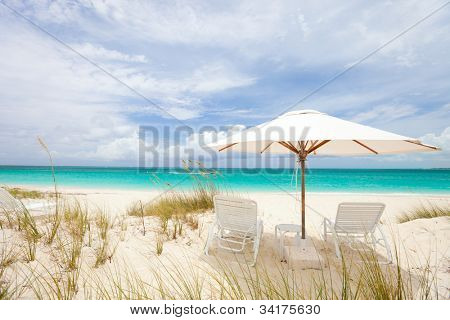 Two chairs under umbrella on stunning Caribbean beach