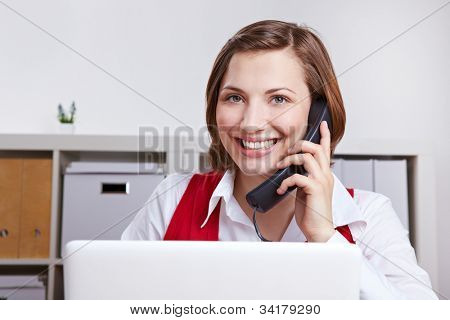 Happy woman in office calling the customer support hotline