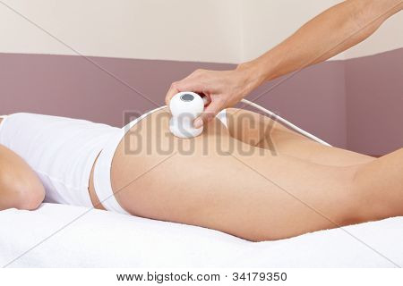 Hand giving woman electrical massage at buttocks in spa