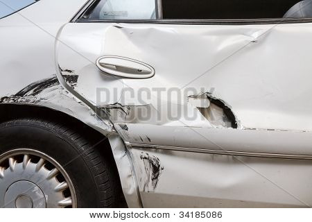 Profile View Of A Dented Car With A Hole