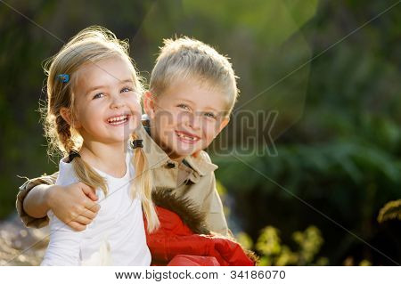 Portrait of adorable brother and sister smile and laugh together while sitting outdoors. happy lifestyle kids
