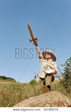 Adventure explorer treasure map boy with wooden sword plays outdoors in a field having fun