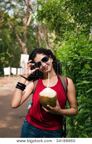 Indian young girl enjoying coconut water
