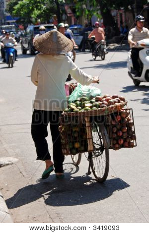 Woman Carrying A Basket Of Fruit In Hanoi