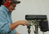 stock photo of blue-collar-worker  - Distinguished senior blue collar worker working on drill press - JPG