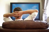 picture of couch potato  - Man sitting on a sofa watching tv with hands folded behind his head - JPG