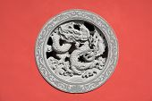 Stone dragon relief - window made of decorated stone relief, ornaments and relief on the red wall fr poster