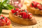 picture of antipasto  - Fresh homemade crispy Italian antipasto called Bruschetta topped with tomato garlic and basil on wooden board  - JPG