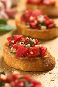 stock photo of antipasto  - Fresh homemade crispy Italian antipasto called Bruschetta topped with tomato garlic and basil on wooden board  - JPG