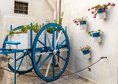 A Wooden Car Painted White And Blue Decorated With Flowers In Polignano A Mare. Apulia, Italy poster