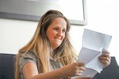 Portrait Of Woman Enjoying Good News In Writing. The Girl Reads A Letter With Good News Sitting On T poster