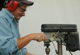 pic of blue-collar-worker  - Distinguished senior blue collar worker working on drill press - JPG