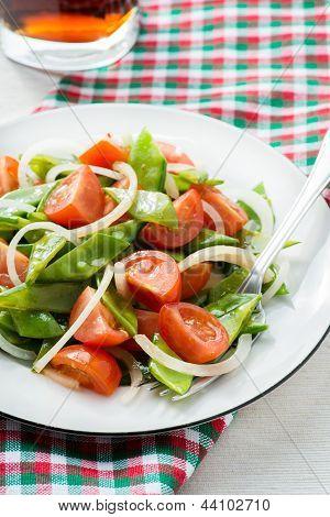 Fresh snow peas and tomato salad on plate