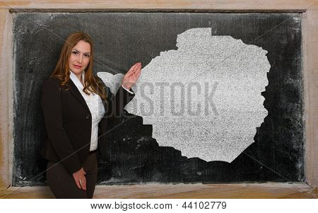 Teacher Showing Map Of Zimbabwe On Blackboard
