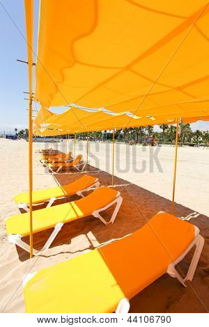 Empty yellow umbrellas and colorful sunloungers on the sandy beach in south Spain over blue bright sky near sea shore, tourism and vacation background