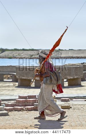 Religious Hindu Man Walking Carrying A Flag
