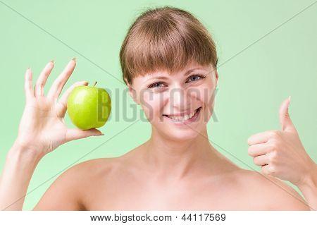 Junge glücklich lächelnde Frau mit Apfel und Daumen hoch