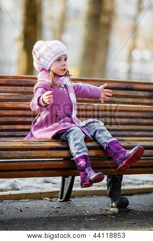 Young Girl Sitting On A Wooden Bench