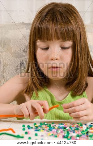 Young girl making a bead bracelet