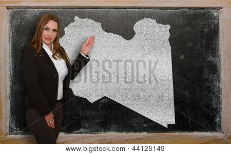 Teacher Showing Map Of Lybia On Blackboard