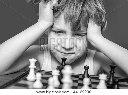 Boy playing chess, thinking how to make a move.