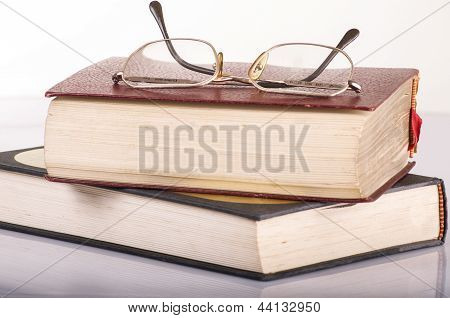 pile of books and glasses