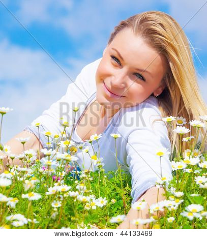 Attractive blond girl lying down on daisy glade in sunny day, beautiful white flowers, spring vacation concept