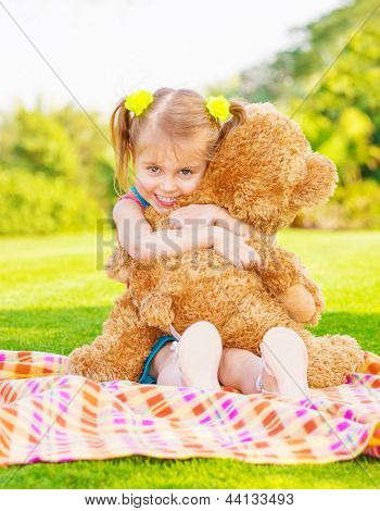 Cute little happy girl hugging big brown teddy bear and sitting down on green grass meadow, spring season