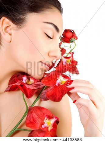 Side view of sensual arabic woman with closed eyes isolated on white background, fresh red orchid flowers, luxury spa salon, joy and pleasure concept