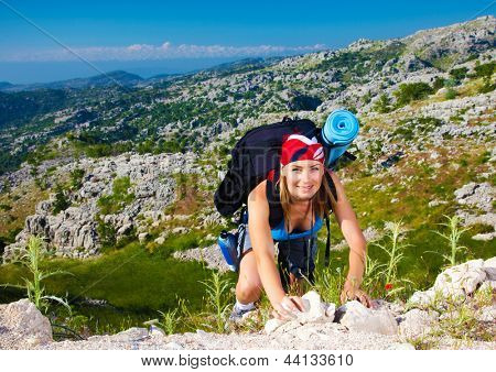 Cute teen girl clambering on the top of mountain, extreme adventure, summer traveling, freedom concept