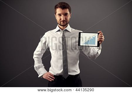 confident man in formal wear showing growth chart over dark background
