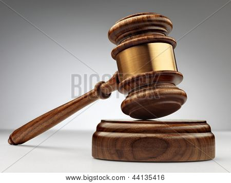 A wooden judge gavel and soundboard on grey