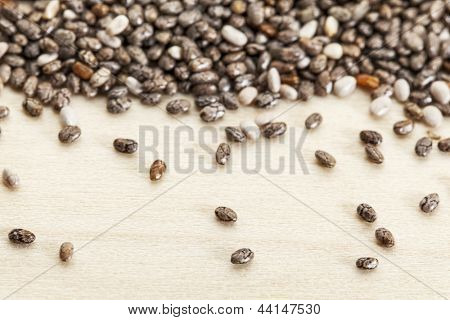 chia seeds  on poplar wood surface -  a close-up with a shallow depth of field